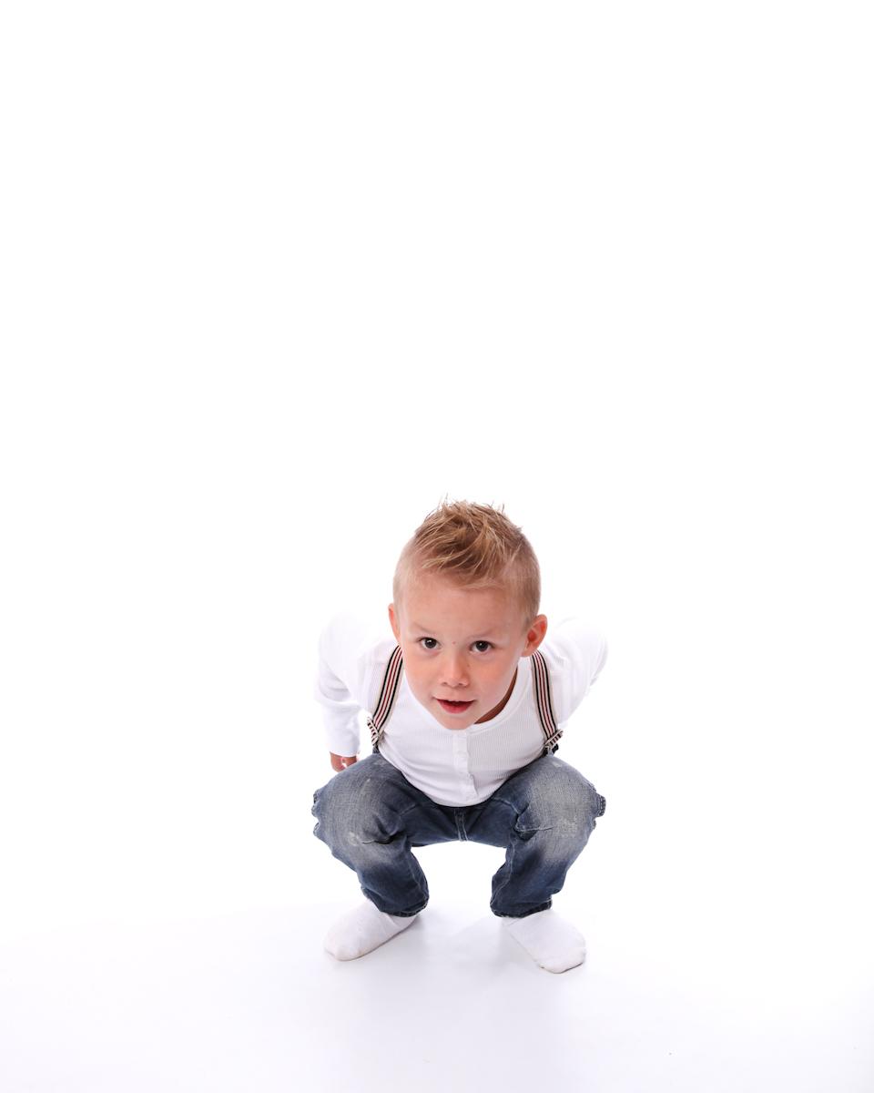Fotografi på ung pojke med hängslen. Sitter på golvet och tittar in i kameran.