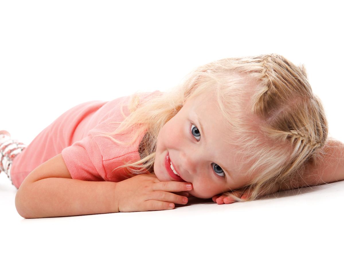 Spontant porträtt på barn på golvet. Flicka med klänning.