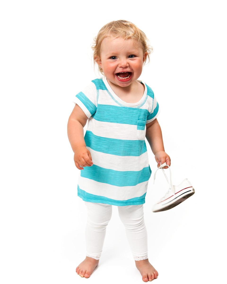 Liten barfota tjej i randig klänning. Håller i ett par skor. Fotografi från Studio Jätteliten. Fotograf Filip Leo