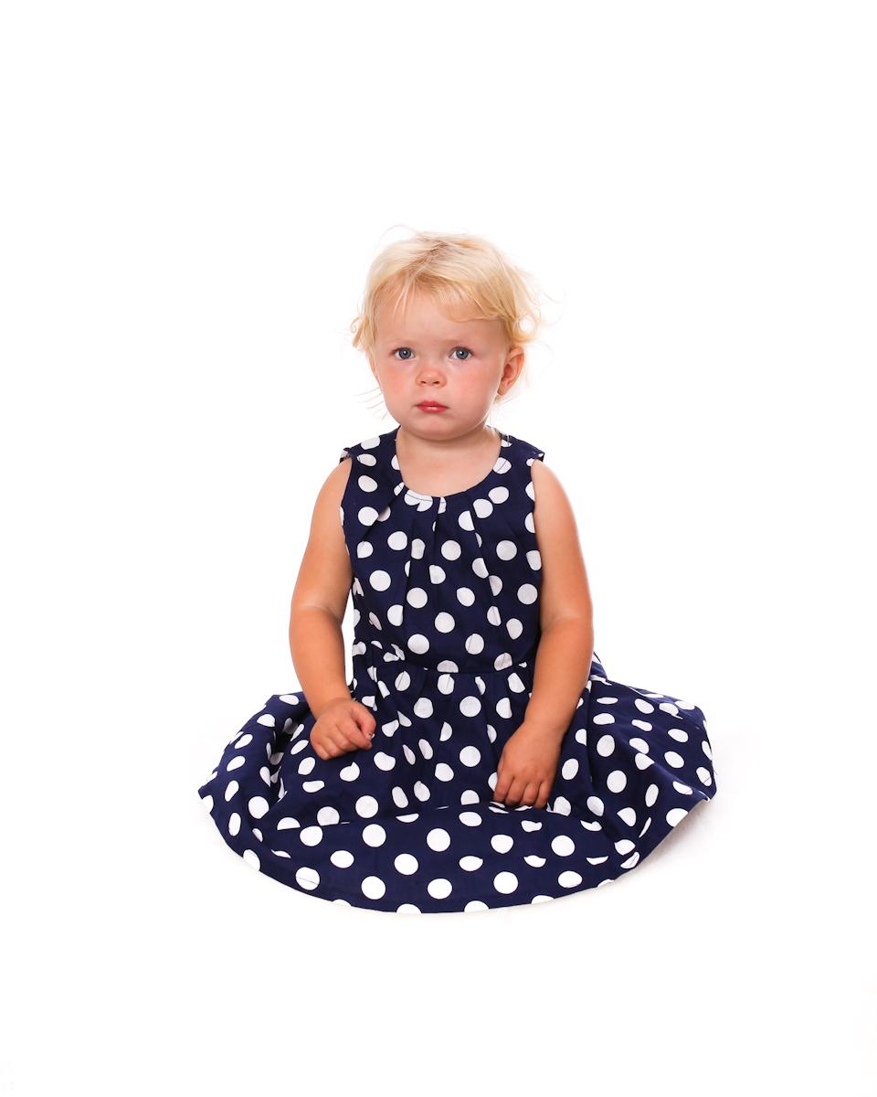 Flicka i blåprickig klänning. Barnfoto från Studio Jätteliten. Fotograf Filip Leo