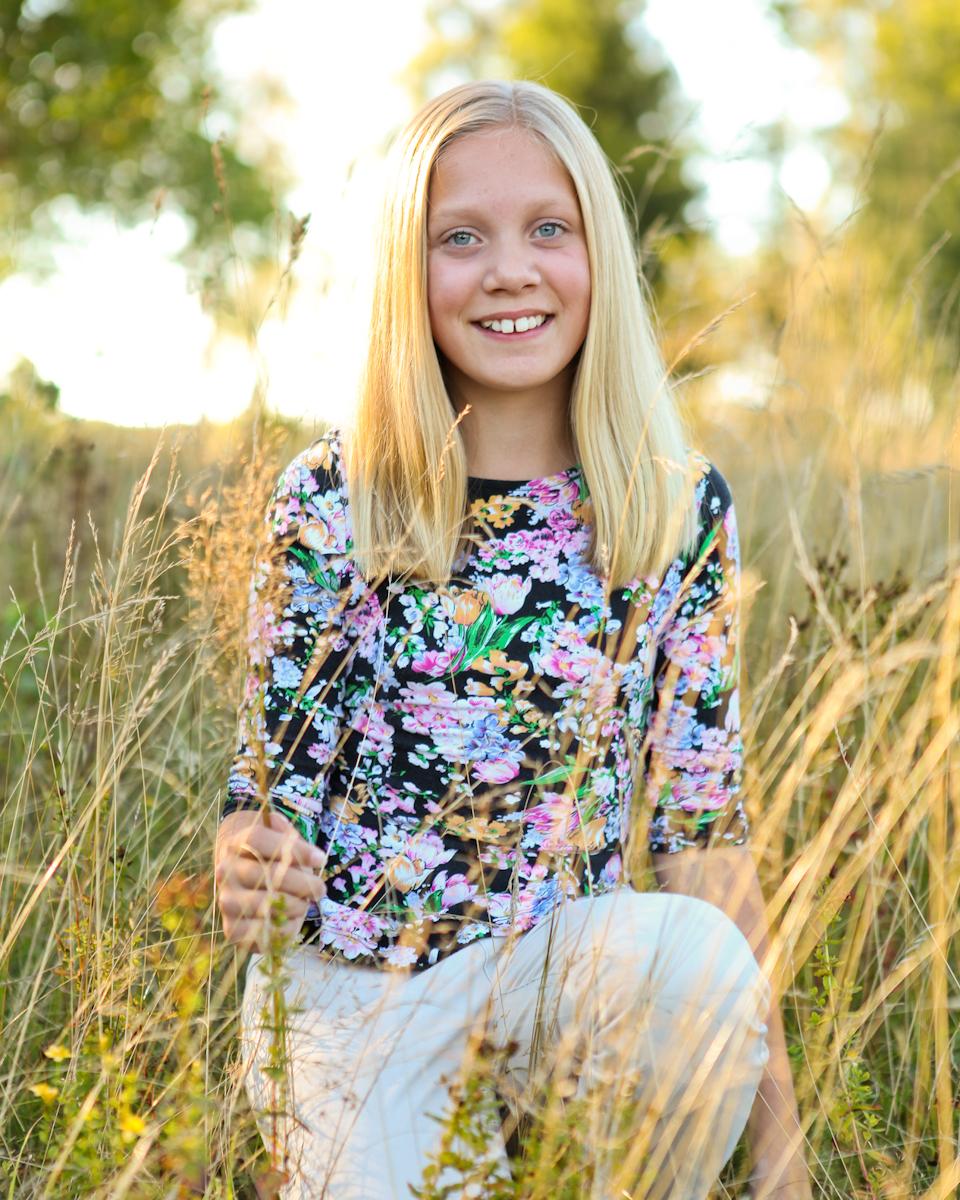 Motljusbild på ung tjej med blommor i hästhagen. Sommarkväll vid Studio Jätteliten. Fotograf Filip Leo, Linköping.
